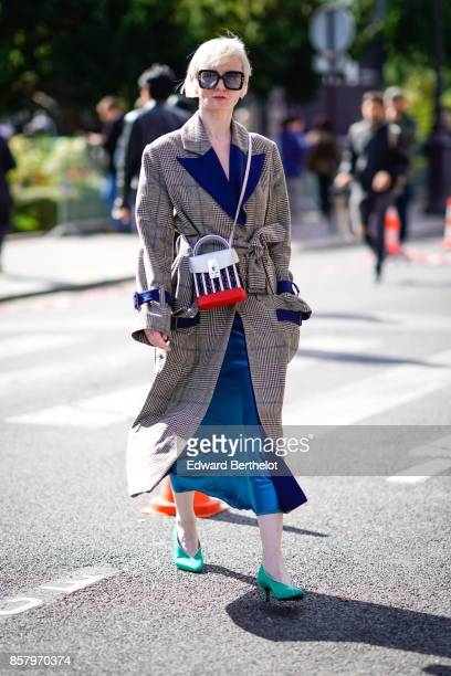 A guest wears sunglasses a tartan coat a blue skirt blue shoes outside Moncler during Paris Fashion Week Womenswear Spring/Summer 2018 on October 3...