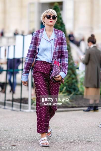 A guest wears sunglasses a tartan purple blazer jacket a blue shirt purple pants sandals shoes outside Moncler during Paris Fashion Week Womenswear...