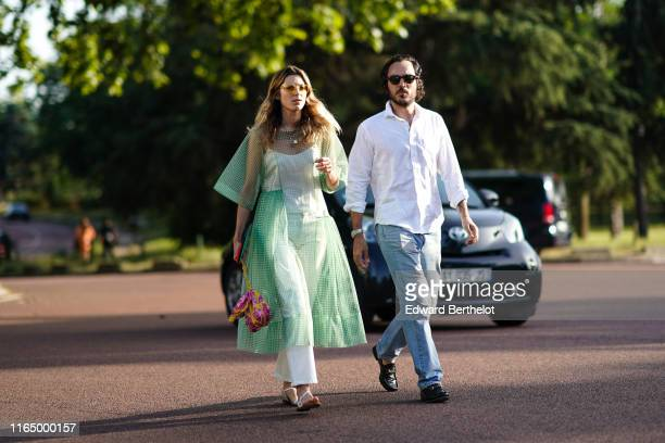 Guest wears sunglasses, a transparent green checkered flowing dress over a white strappy top and white pants, white strappy flat sandals, a fuchsia...