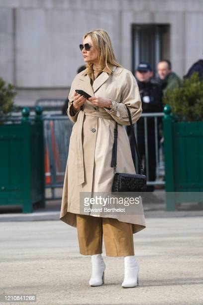 Guest wears sunglasses, a trench coat, a Karl Lagerfeld leather bag, brown pants, white boots, outside Chanel, during Paris Fashion Week - Womenswear...