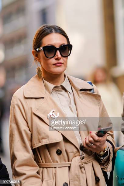 A guest wears sunglasses a trench coat and a Chanel brooch during London Fashion Week February 2018 on February 17 2018 in London England