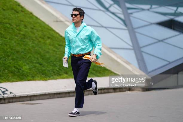 Guest wears sunglasses, a turquoise blue shirt, a brown leather belt, dark blue pants, white socks, sneakers, outside Kenzo, during Paris Fashion...