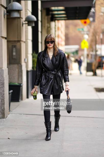 A guest wears sunglasses a turtleneck pullover a black leather jacket black pants leather boots a bag during New York Fashion Week Fall Winter 2020...