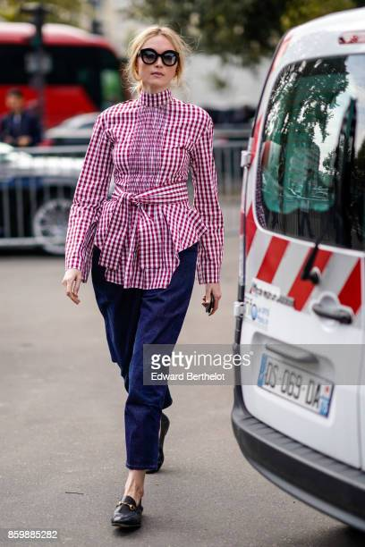 A guest wears sunglasses a turtleneck red gingham top with a belt bow navy blue pants black moccasins outside the Dries Van Noten show during Paris...