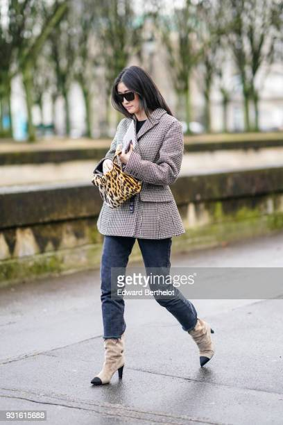 A guest wears sunglasses a tweed jacket a leopard pattern handbag blue jeans and beige and black boots outside Valentino during Paris Fashion Week...