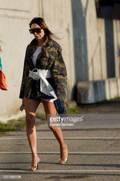 Guest wears sunglasses, a white belt, a green khaki military camouflage jacket, golden high heel shoes, a bag, outside Alberta Ferretti, during Milan...