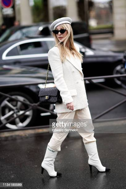 A guest wears sunglasses a white beret hat a white tweed jacket white pants a black Chanel bag black and white Chanel boots outside Miu Miu during...