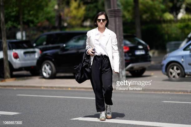 A guest wears sunglasses a white blazer jacket a bag black pants a white shirt sneaker shoes outside Rick Owens during Paris Fashion Week Menswear...