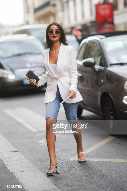 A guest wears sunglasses a white blazer jacket blue denim ripped shorts shoes outside Ralph Russo during Paris Fashion Week Haute Couture Fall/Winter...