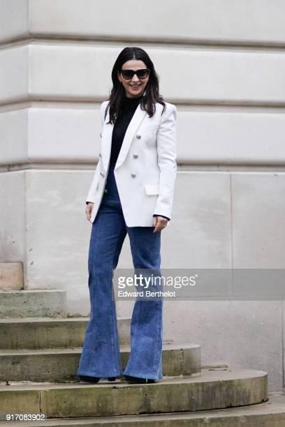 A guest wears sunglasses a white blazer jacket blue flare denim jeans outside Balmain during Paris Fashion Week Menswear Fall Winter 20182019 on...