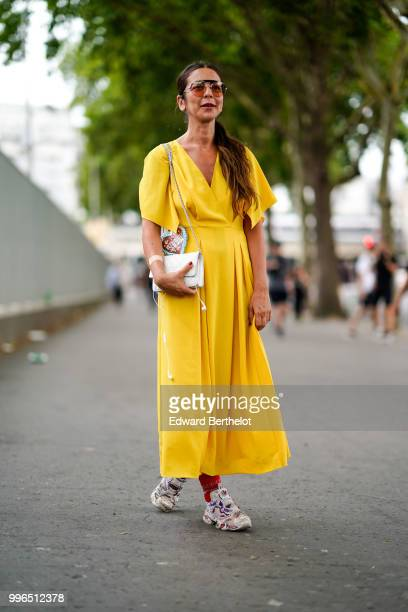 Guest wears sunglasses, a white Chanel bag, a yellow dress, sneakers shoes , outside Vetements, during Paris Fashion Week Haute Couture Fall Winter...