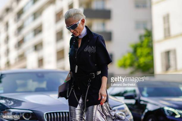 A guest wears sunglasses a white choker a black jacket silver pants outside 1017 ALYX 9SM during Paris Fashion Week Menswear SpringSummer 2019 on...