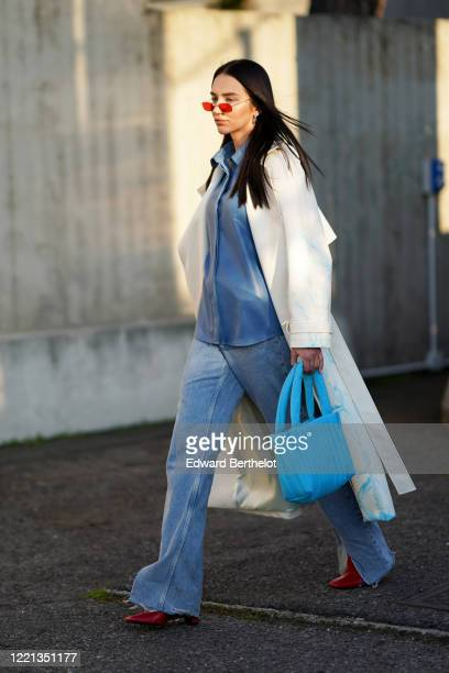 Guest wears sunglasses, a white coat, a blue jacket, blue denim flared ripped jeans, a blue bag, red pointy shoes, outside Alberta Ferretti, during...
