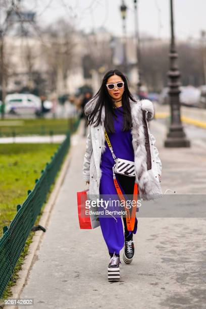 A guest wears sunglasses a white coat with fur purple pants an OffWhite bag during Paris Fashion Week Womenswear Fall/Winter 2018/2019 on March 1...