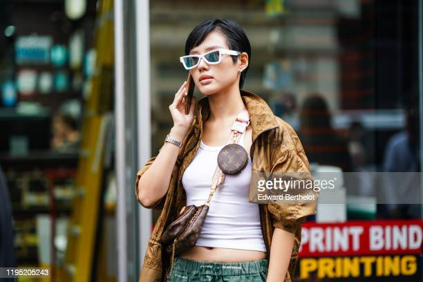 Guest wears sunglasses, a white cropped tank top, a Vuitton bag, a Vuitton monogram brown long coat, outside JW Anderson, during London Fashion Week...