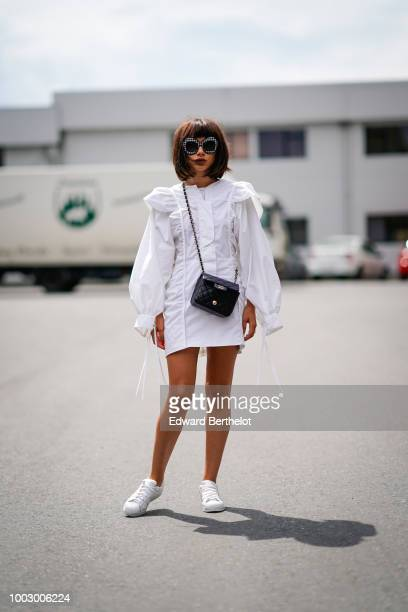 A guest wears sunglasses a white dress a Chanel bag white sneakers during Feeric Fashion Week 2018 on July 20 2018 in Sibiu Romania