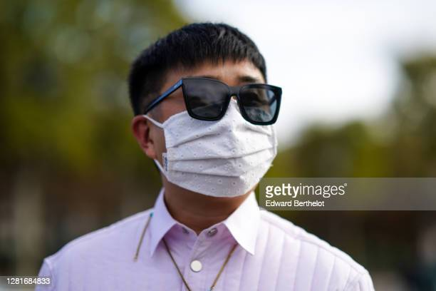 Guest wears sunglasses, a white face mask, outside Chanel, during Paris Fashion Week - Womenswear Spring Summer 2021, on October 06, 2020 in Paris,...
