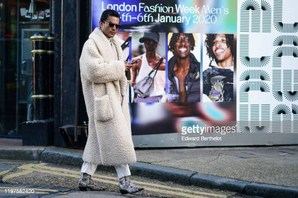 A guest wears sunglasses a white fluffy long coat pointy boots with printed snake patterns white pants during London Fashion Week Men's January 2020...