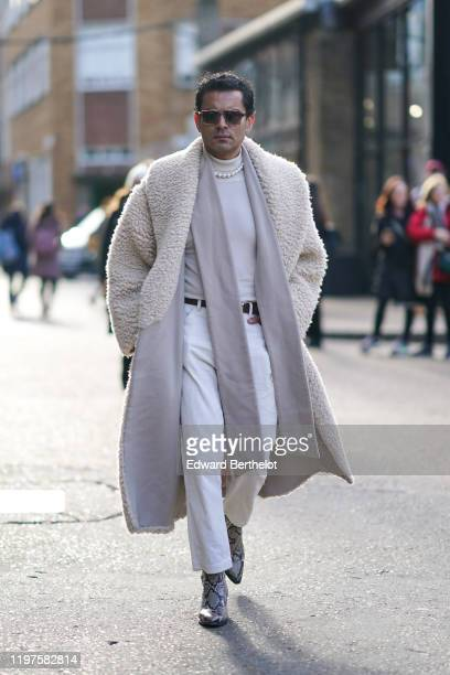 A guest wears sunglasses a white fluffy long coat pointy boots with printed snake patterns white pants a pearl necklace a white turtleneck a belt...