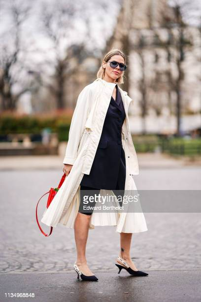 A guest wears sunglasses a white hooded trench coat with a flowing pleated bottom skirt a black jacket black short pants black pointy slingback Dior...