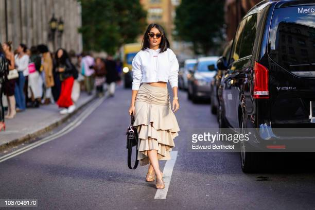 A guest wears sunglasses a white hoodie sweater top a beige ruffled skirt beige shoes a bag during London Fashion Week September 2018 on September 14...