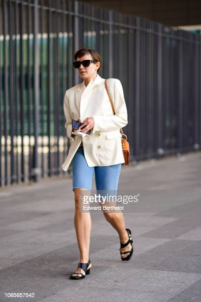 A guest wears sunglasses a white jacket blue shorts black shoes outside Issey Miyake during Paris Fashion Week Menswear SpringSummer 2019 on June 21...