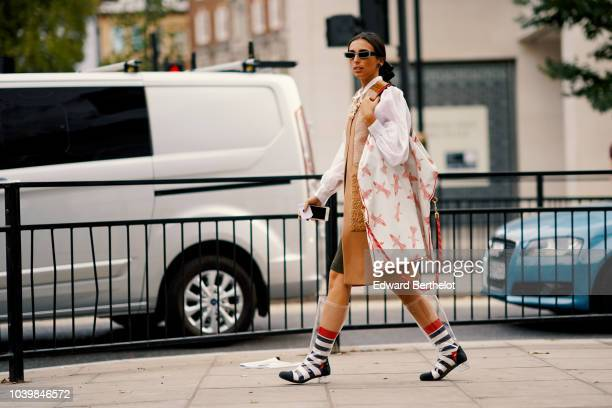A guest wears sunglasses a white jacket with red printed stars transparent plastic boots black and white striped boots during London Fashion Week...