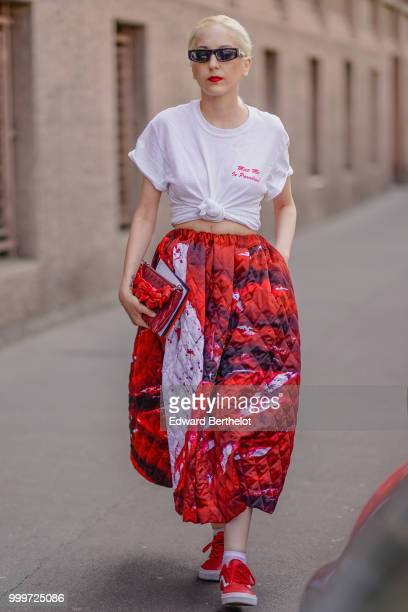 A guest wears sunglasses a white knotted tshirt a red puffer skirt red sneakers shoes outside Wooyoungmi during Paris Fashion Week Menswear...