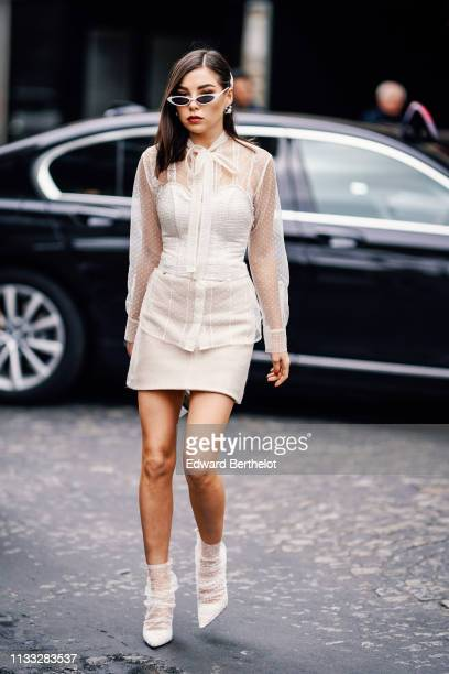 A guest wears sunglasses a white lace dress a white corset white lace shoes a circular bag outside Elie Saab during Paris Fashion Week Womenswear...