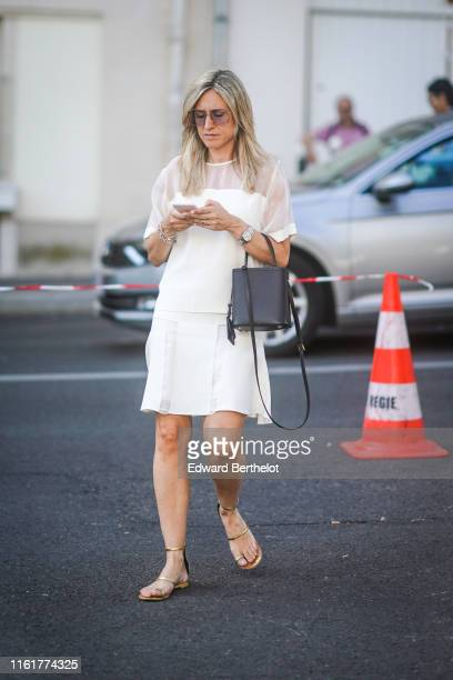 Guest wears sunglasses, a white lace mesh dress, a black bag, a watch, shoes, outside Acne, during Paris Fashion Week - Haute Couture Fall/Winter...