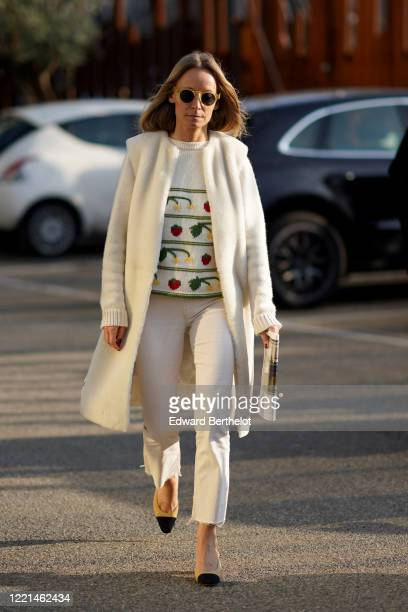 Guest wears sunglasses, a white long jacket, a pullover with printed fruits, white pants, Chanel slingback shoes, outside Alberta Ferretti, during...