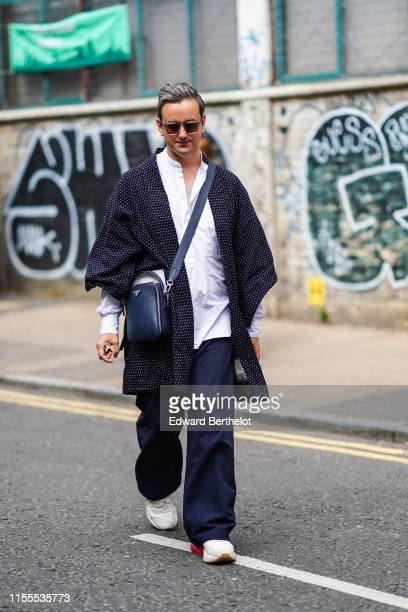 A guest wears sunglasses a white mandarin collar shirt a black kimonostyle light coat a black Prada bag navy blue pants white sneakers during London...