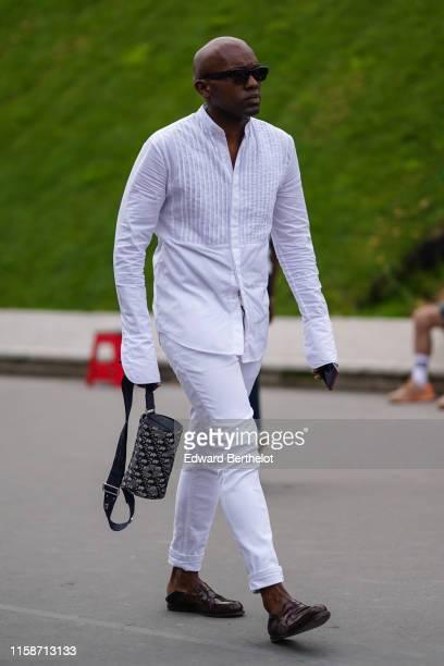 A guest wears sunglasses a white Nehru collar shirt white cuffed pants a Christian Dior monogram bag brown moccasins outside Kenzo during Paris...