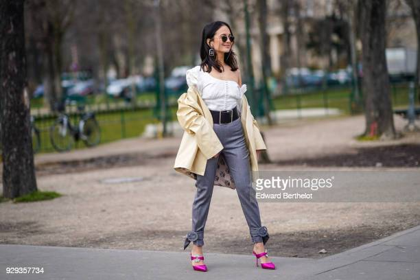 A guest wears sunglasses a white off shoulder top a jacket a large belt gray pants pink shoes outside Chanel during Paris Fashion Week Womenswear...