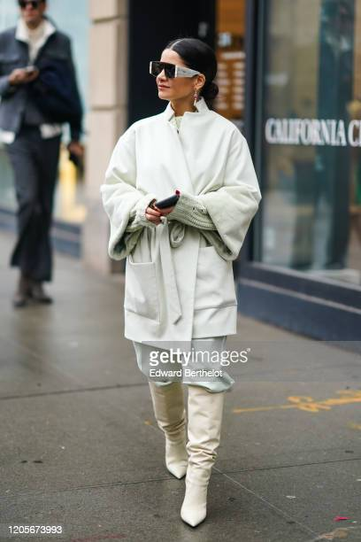 Guest wears sunglasses, a white oversized jacket, a wool pullover, leather pointy boots, earrings, during New York Fashion Week Fall Winter 2020, on...