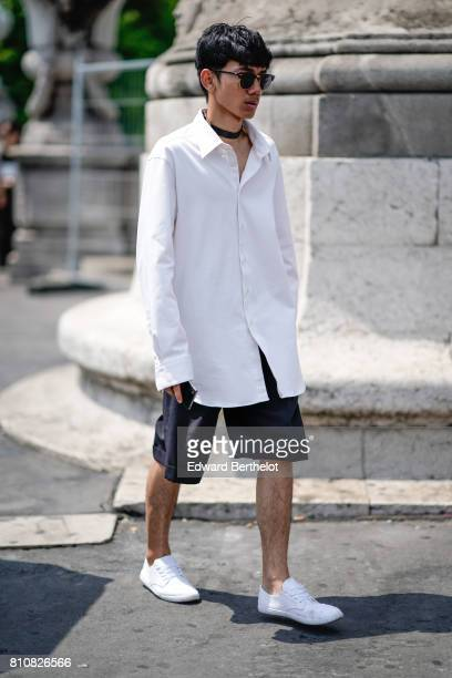 A guest wears sunglasses a white oversized shirt black shorts white sneakers outside the Icosae show during Paris Fashion Week Menswear Spring/Summer...