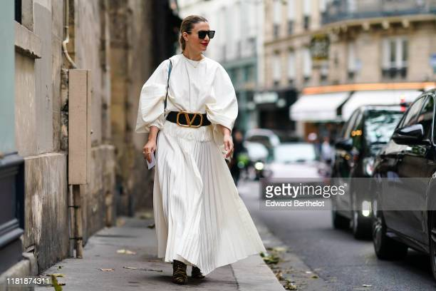 Guest wears sunglasses, a white pleated dress, a Valentino large belt with logo, outside Thom Browne, during Paris Fashion Week - Womenswear Spring...