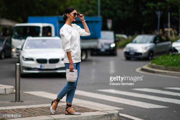 Guest wears sunglasses, a white puff shoulders top, a beaded bag, blue denim jeans, gray shoes, outside the Fendi show during Milan Fashion Week...