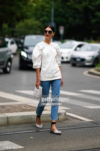 A guest wears sunglasses a white puff shoulders top a beaded bag blue denim jeans gray shoes outside the Fendi show during Milan Fashion Week...