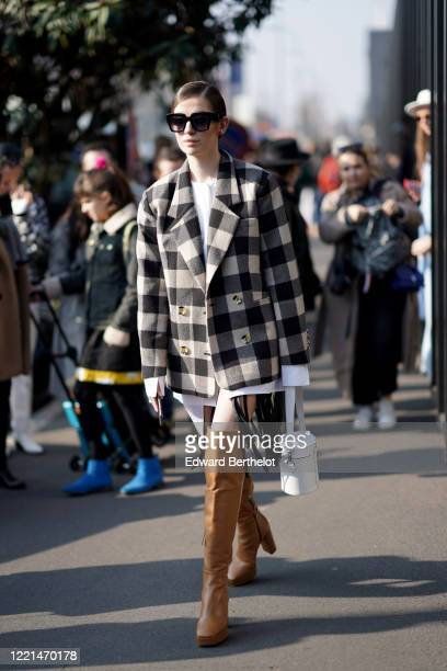 Guest wears sunglasses, a white shirt, a black and white checked oversized blazer jackey, outside Gucci, during Milan Fashion Week Fall/Winter...