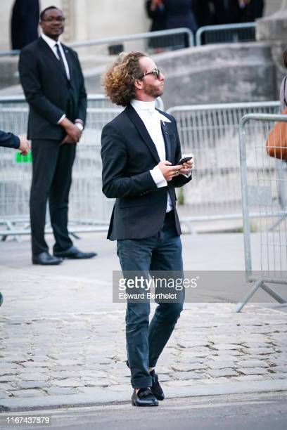 A guest wears sunglasses a white shirt a black jacket blue cuffed jeans black moccasins with a bow outside Karl for Ever Tribute to Karl Lagerfeld at...