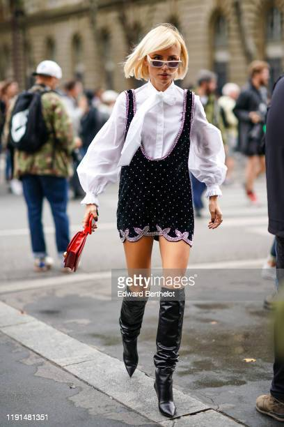 Guest wears sunglasses, a white shirt, a black short stud dress, a red bag, black leather high boots, outside Redemption, during Paris Fashion Week -...