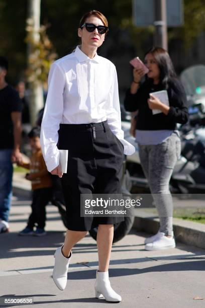 A guest wears sunglasses a white shirt a black skirt white shoes outside Nina Ricci during Paris Fashion Week Womenswear Spring/Summer 2018 on...