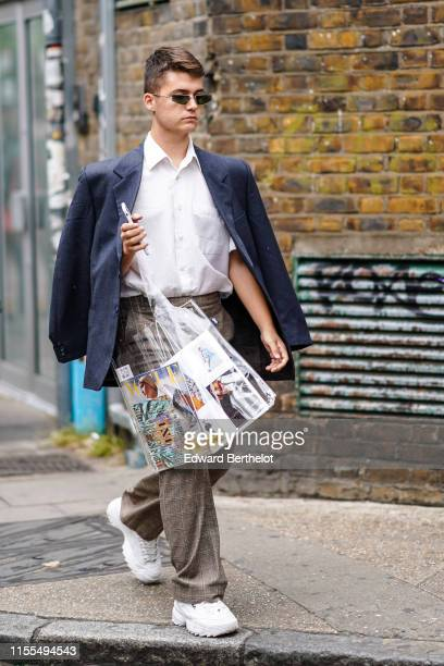 A guest wears sunglasses a white shirt a deep blue jacket light brown Prince of Wales check pants white Fila sneakers during London Fashion Week...