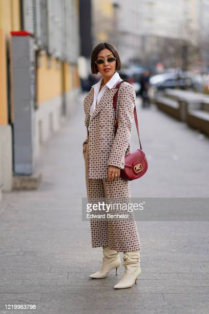 Guest wears sunglasses, a white shirt, a jacket with printed patterns, a red leather bag from Etro, flare pants, white leather pointy boots, outside...