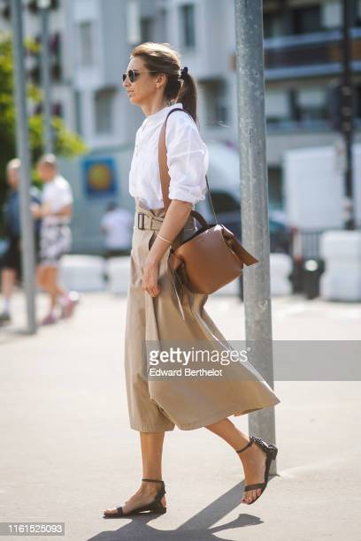 A guest wears sunglasses a white shirt a light khaki skirt a brown Acne Studios bag black anklestrap flat sandals outside Acne during Paris Fashion...