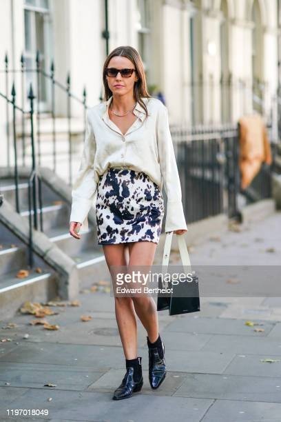 A guest wears sunglasses a white shirt a necklace a black and white cow print skirt black leather shiny pointy shoes a black bag with white handle...