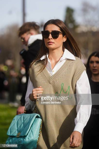 Guest wears, sunglasses, a white shirt, a v-neck long sleeveless wool pullover, a turquoise quilted Chanel bag, toutside Chanel, during Paris Fashion...