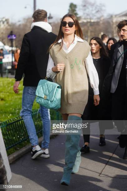 Guest wears, sunglasses, a white shirt, a v-neck long sleeveless wool pullover, a turquoise quilted Chanel bag, thigh high boots, outside Chanel,...