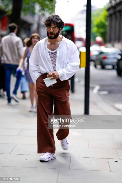 A guest wears sunglasses a white shirt a white mesh top brown flared pants white sneakers during London Fashion Week Men's June 2018 on June 10 2018...